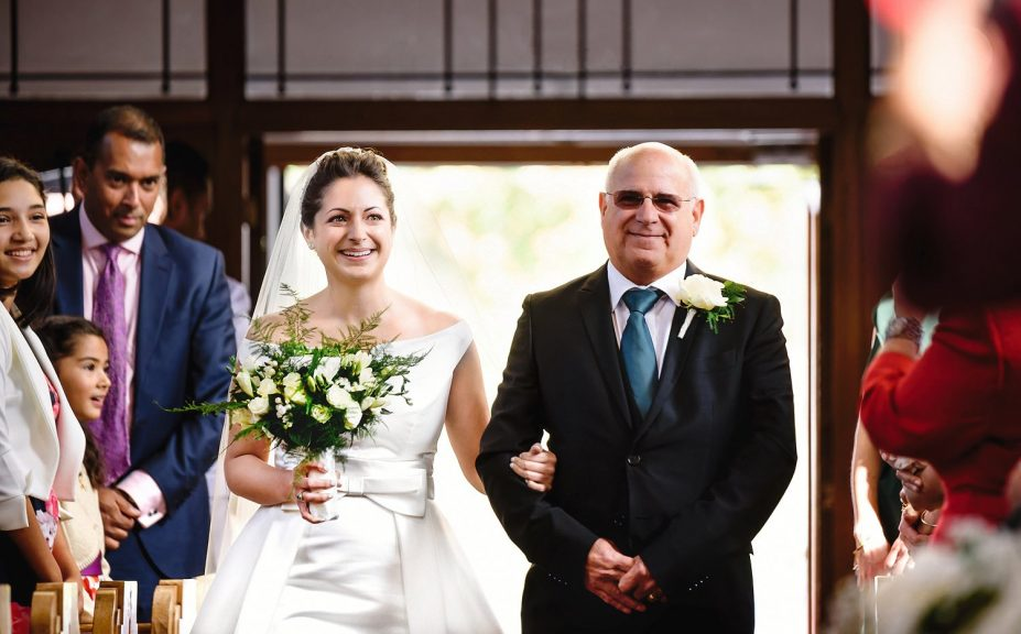 Bride walking down the aisle with father at her church wedding ceremony