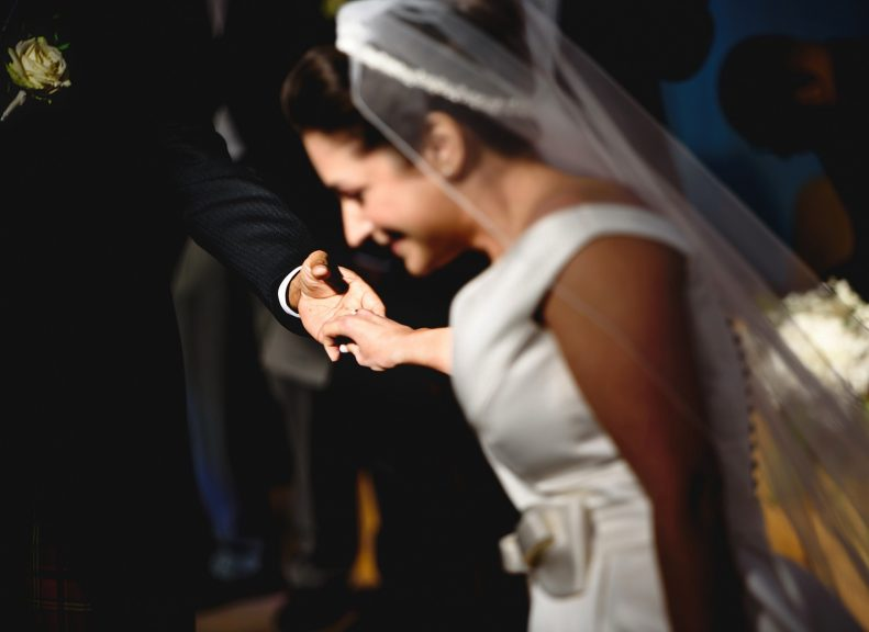 Bride and groom holding hands at church ceremony wedding in Surrey