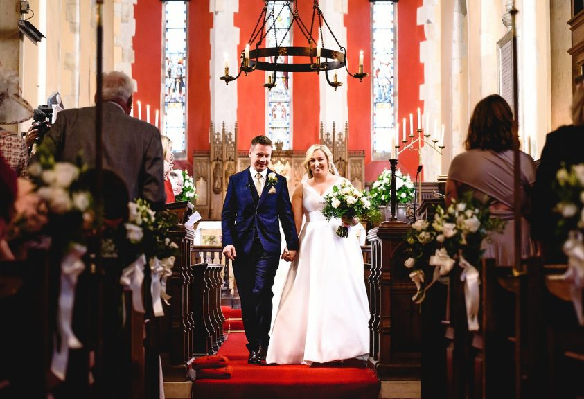 Bride and groom walking down the aisle at Braxted Park church ceremony