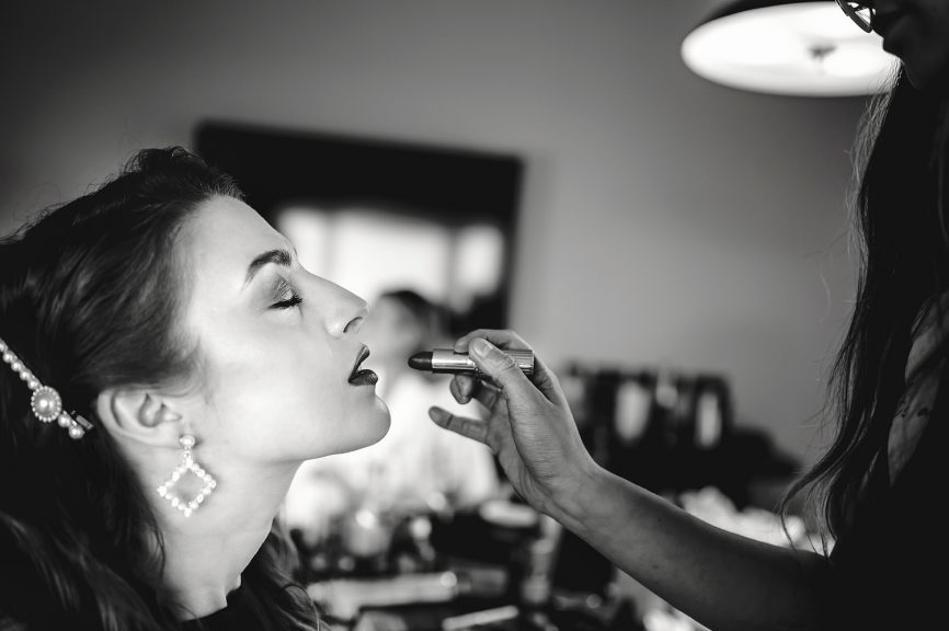 Bride getting ready with lipstick from makeup artist