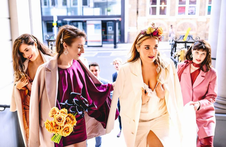 Bride walking into church with her bridesmaids taken by London Wedding Photographer