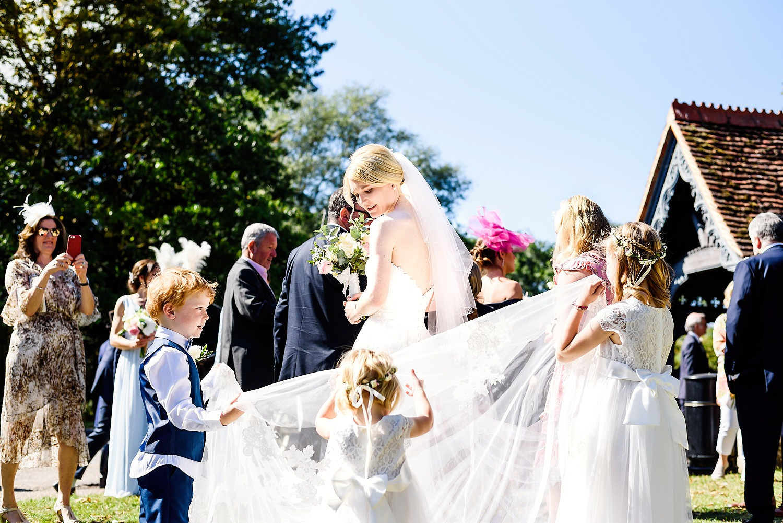 children holding brides dress outside a church