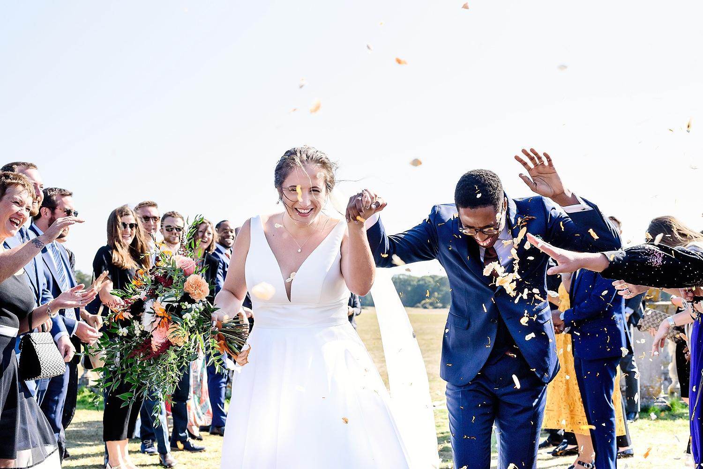 bride and groom walking through confetti line