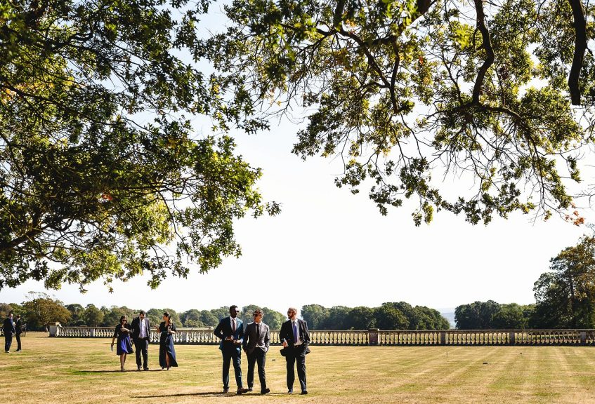 Wedding guests walking at Pylewell Park wedding venue taken by a fine art wedding photographer