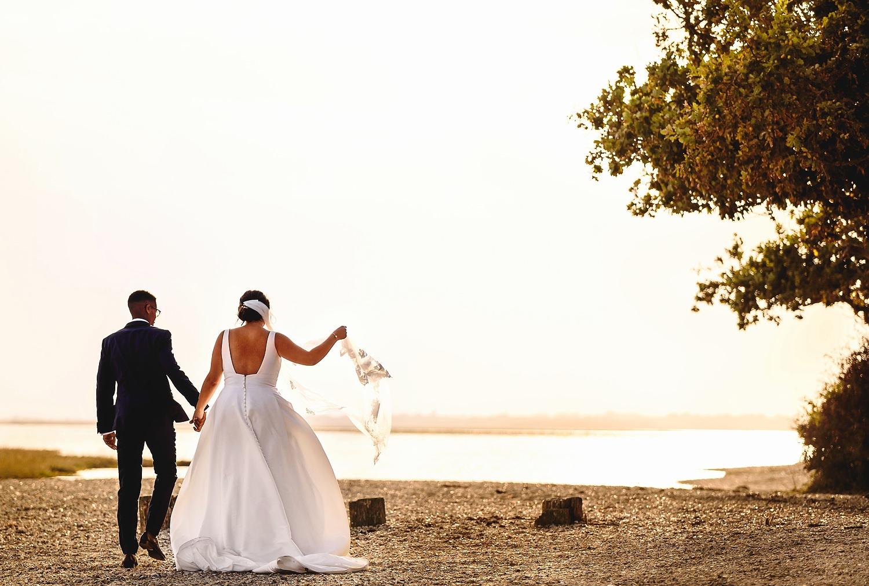 Bride and groom walking on the beach at Pylewell Park wedding venue
